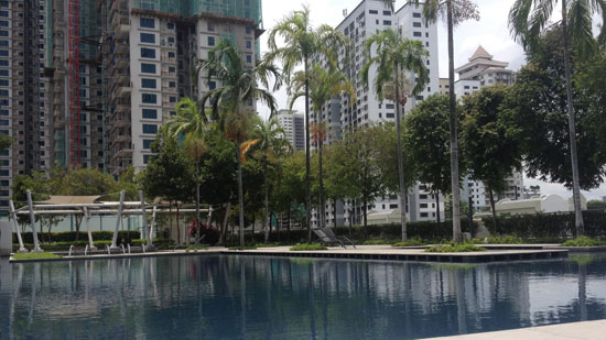 "Picture of a pool surrounded by palm trees and tall apartment buildings with white text saying ""A year of housesitting in SE Asia"""