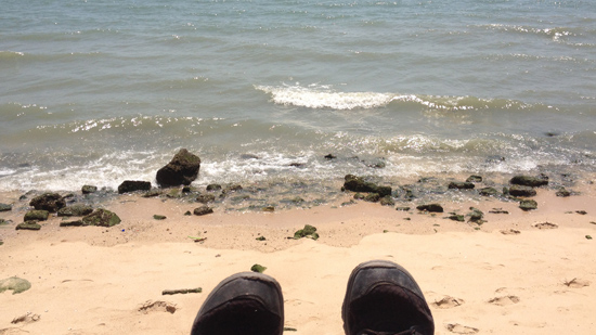 Photo of a rocky beach with white waves and a pair of shoes in the foreground.