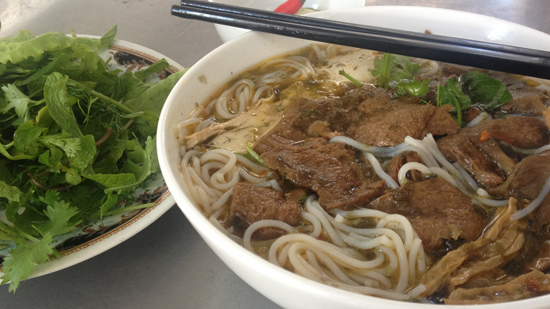 Photo contains a bowl of noodles with veg beef, mushrooms, sprouts, and other vegetables. On a separate plate, there are fresh herbs and leafy greens.