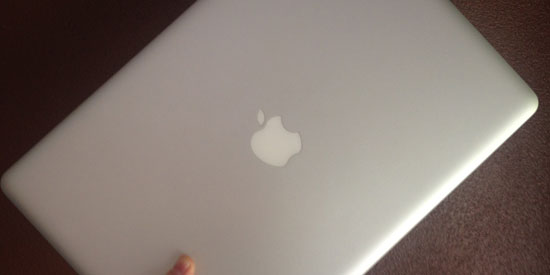 Image contains a grey MacBook Pro being held at an angle by a hand against a brown background.