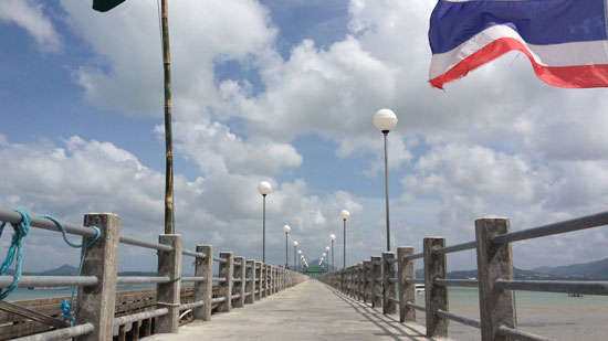 Image contains a wooden pier that narrows toward the centre of the image. Above it, there is a blue sky with white clouds. To the right, the Thailand flag can be seen with blue, white, and red stripes.