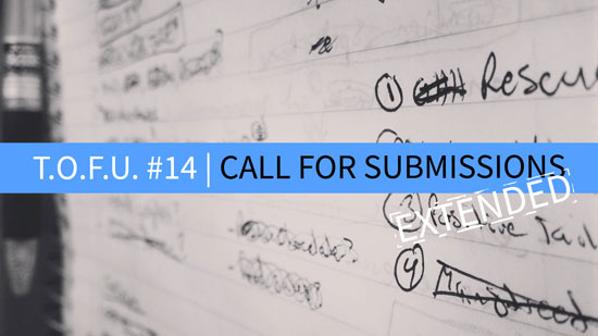 "Image contains a notepad with illegible text in black ink and a pen on the left-hand side. In the foreground, there is text in the middle of the screen on a strip of blue that says ""T.O.F.U. #14 