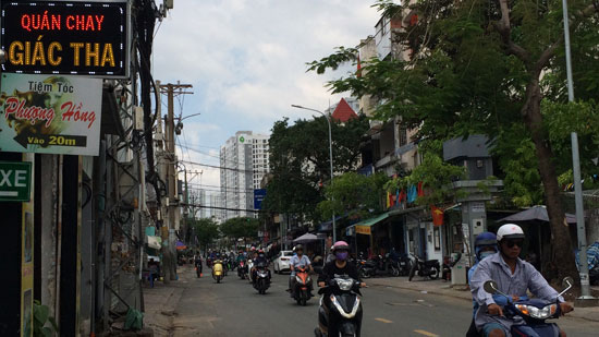"Image is a photo of a Saigon street with numerous scooters coming towards the camera. Shops are visible on both sides of the street, and a small neon sign in the top left-hand corner says ""Quán Chay Giác Tha""."