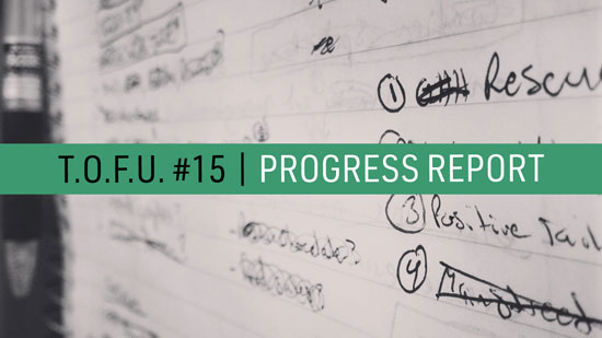 "Image contains a notepad with illegible text in black ink and a pen on the left-hand side. In the foreground, there is text in the middle of the screen on a strip of light green that says ""T.O.F.U. #15 