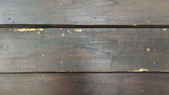 Image contains a photo of wooden siding with a dark brown colour. Various blemishes are visible on the boards.