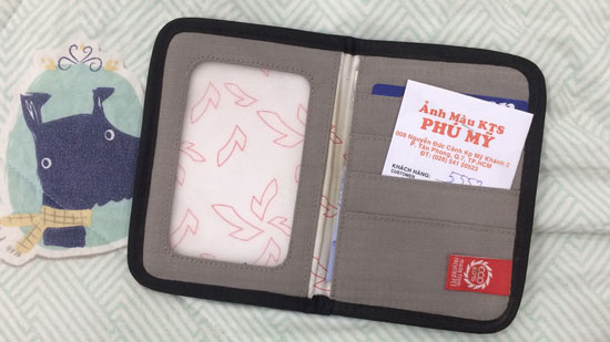 Image contains a photo of a large wallet. On the left-hand side of the wallet, there is an empty pocket. On the right-hand side, there are a number of slots for cards. In one slot, a small white envelope can be seen with words written in Vietnamese on it. In the background, there is a bedspread with a light green pattern. To the left of the wallet, there is a cartoon dog staring at the wallet.
