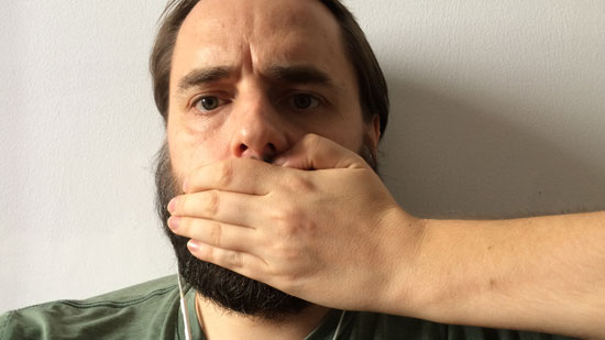 Photo contains a man with a beard looking directly at the camera. From the right-hand side, a hand and arm can be seen, and the hand is covering the man's mouth.