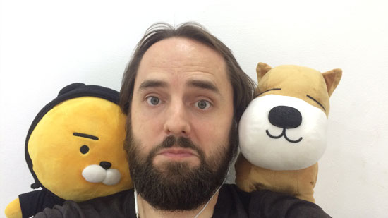 Image contains a photo of a man looking into the camera with an amused look on his face. On both shoulders, he has a stuffed animal.
