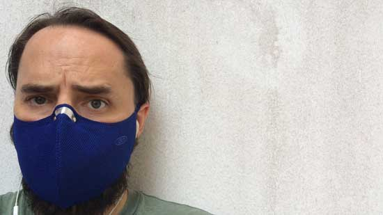Image contains a photo of a man wearing a blue mask around the lower half of his face. The shoulders of the man are visible, and he's standing against a wall that is mostly white.