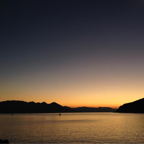 Image contains a photo of a sunset over a large body of water. On the horizon, hills can be seen stretching across most of the frame. The sky is a bright orange near the horizon, and it eventually turns a dark blue near the top of the frame.