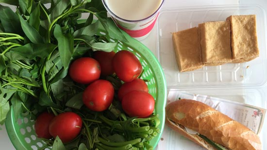 Image contains a photo of a variety of food on a white tabletop. On the left-hand side, in a green plastic basket, there are bright red tomatoes and a bunch of morning glory. To the right of the basket, there is a plastic container of small blocks of fried tofu, and just below that there is a banh mi sandwich.