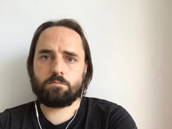 Image contains a photo of a bearded man with long hair looking directly at the camera.