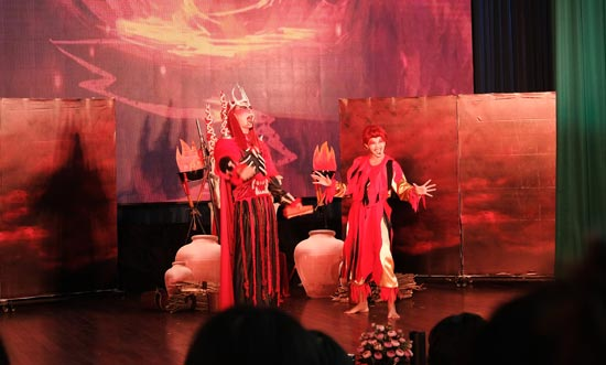 Image contains a photo of a theatrical production involving two characters in a setting similar to Hell. the male character is taller and wears a crown and armour, as well as a cape. The female character is striking a comedic pose with a smile on her face. Much of the photo is in red tones.