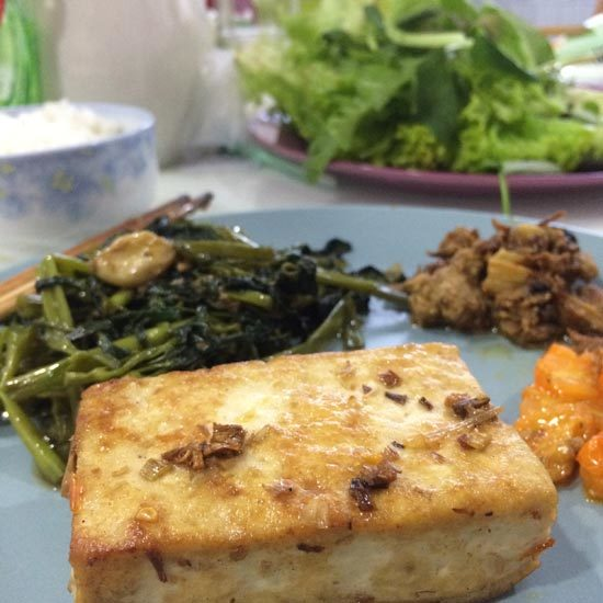 Image contains a photo of a block of fried tofu in the foreground. Behind it there are fried greens, kimchi, and lettuce leafs.