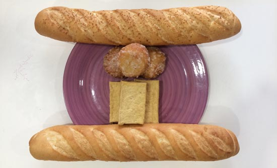 Image contains a photo of a purple plate with blocks of tofu and sugared balls on it. On opposite sides of the plate, there are two baguettes.