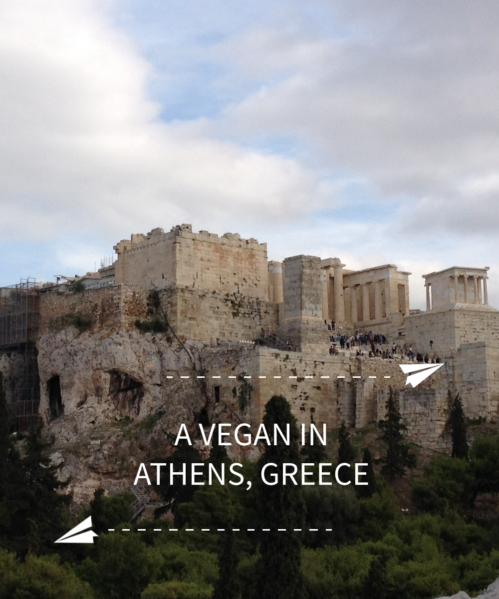 "Image contains a photo of the Acropolis of Athens, Greece. Below the Acropolis, there is white text that says ""A Vegan In Athens, Greece. Above the text, there is a illustration of a small paper plane with a dotted line trailing behind it. On the bottom left-hand side of the text, there is a similar illustration."