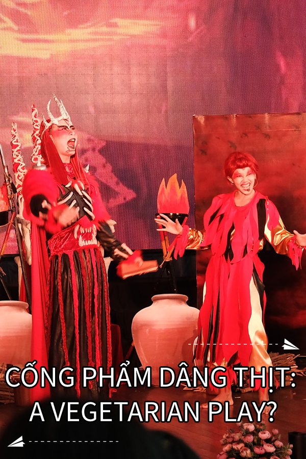 "Image contains a photo of a theatrical production involving two characters in a setting similar to Hell. the male character is taller and wears a crown and armour, as well as a cape. The female character is striking a comedic pose with a smile on her face. Much of the photo is in red tones. In white text at the bottom of the image, there is a title that says ""Cống Phẩm Dâng Thịt: A Vegetarian Play?"". On the right-hand side above the text, there is a small white paper airplane with a dotted line behind it. Below the text and on the left-hand side, there is a similar icon."