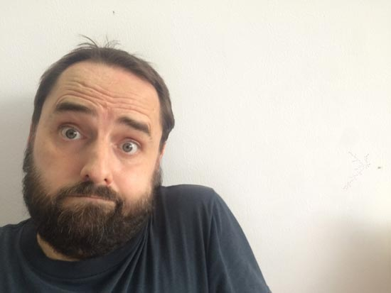 Image contains a photo of a bearded man with a questioning look on his face and his shoulder raised.