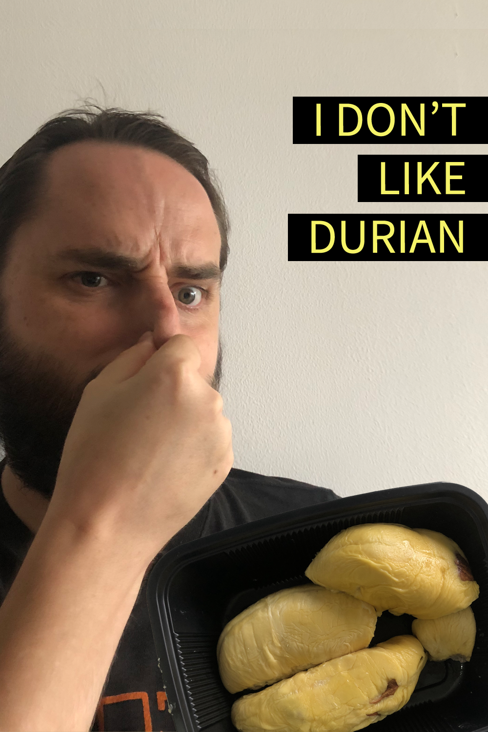"Image contains a photo of a bearded white man pinching his nose and looking unhappy. To the right of the man, there is a black plastic tray of durian, which is a yellowish fruit shaped in large pieces. In the top right-hand side of the image, there is yellow text on black strips that says ""I Don't Like Durian""."