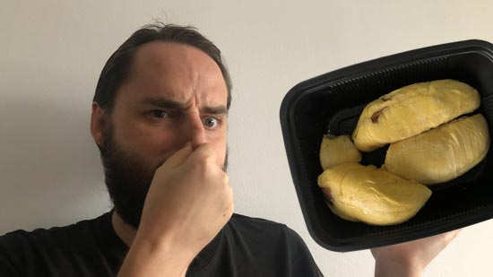 Image contains a photo of a bearded white man pinching his nose and looking unhappy. To the right of the man, there is a black plastic tray of durian, which is a yellowish fruit shaped in large pieces.