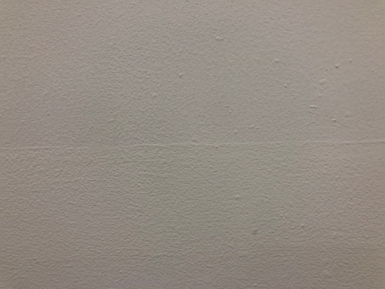 Image contains a photo of a painted white wall with small bumps and a thin line going across the middle.