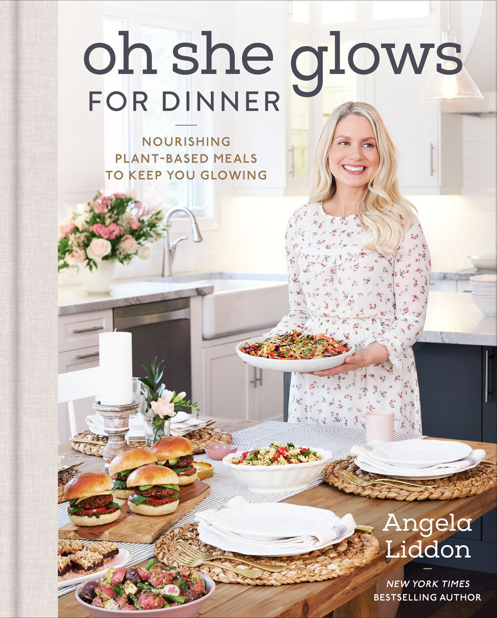 "Image contains a photo of a white woman holding a plate of food in a kitchen. In front of her, there is a wooden table with a number of other dishes. To the left and above her, there is text that says ""Oh She Glows for Dinner"" and ""Nourishing Plant-Based Meals to Keep You Glowing"". In the bottom right-hand side, there is white text that says ""Angela Liddon."""
