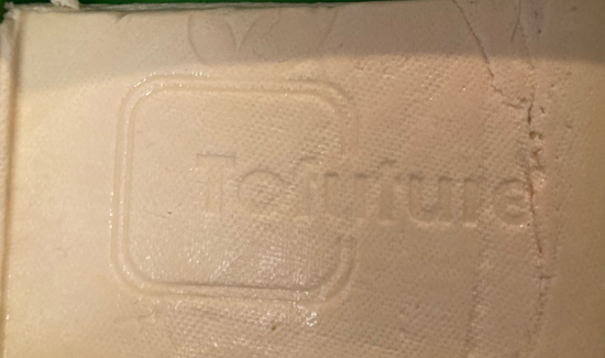 Tofuture logo stamped into tofu after pressing.